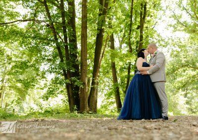 Bruid en bruidegom geven elkaar een kus tijdens fotoreportage in het groen. Bruid draagt een blauwe trouwjurk